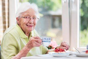 Seniorenassistenz Frieser, Seniorin bei Kaffee und Kuchen